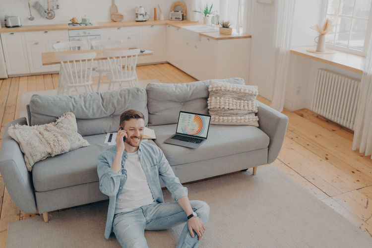 Full length of man using mobile phone while sitting on sofa at home