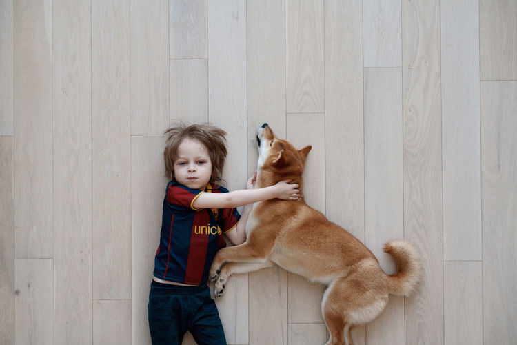 People and pets. top view of funny boy hugging his shiba inu dog