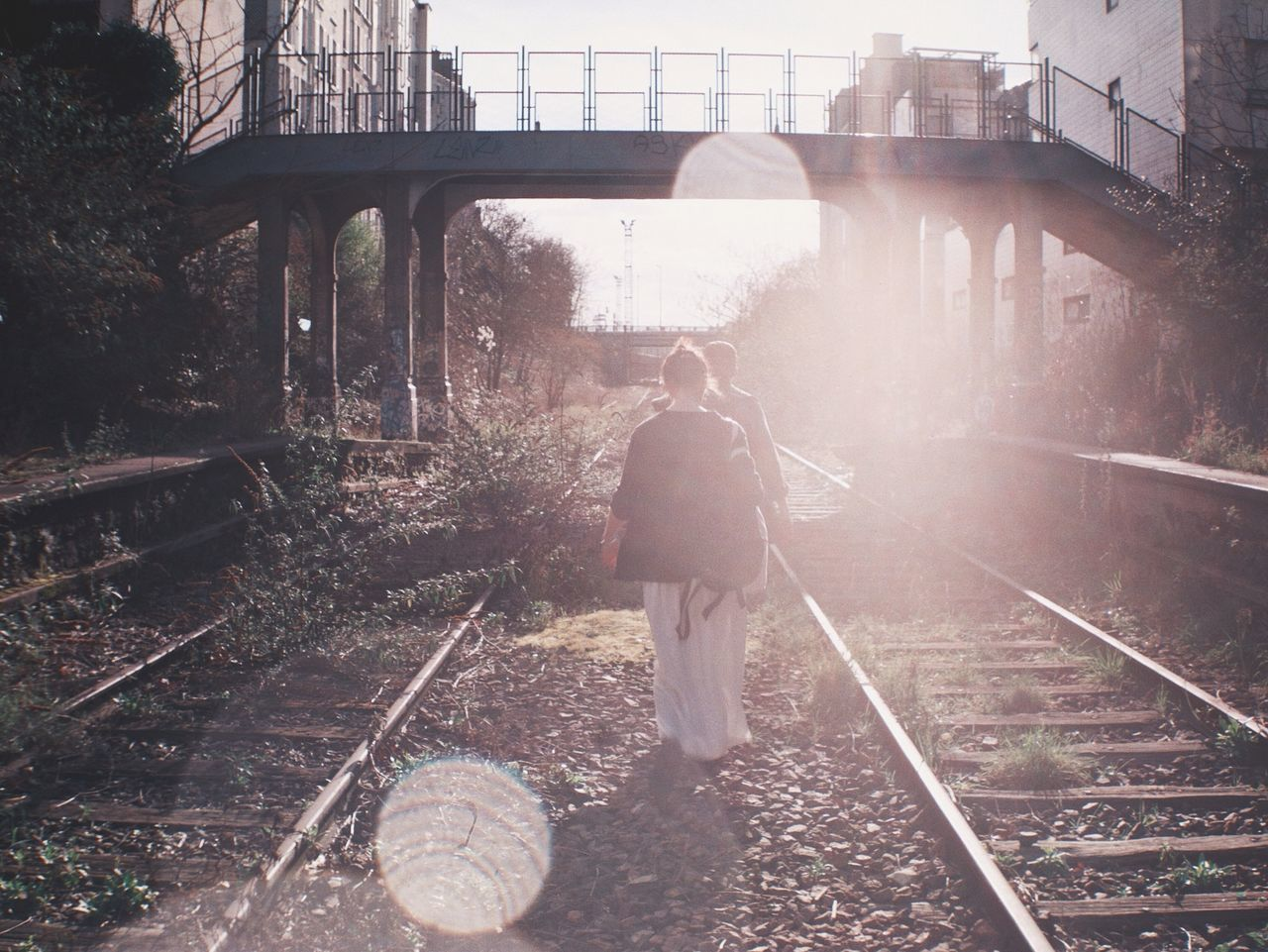 Rear view of people walking by abandoned railroad tracks