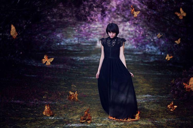 Digital Composite Image Of Woman Wearing Dress Walking On Pathway Amidst Burning Butterflies
