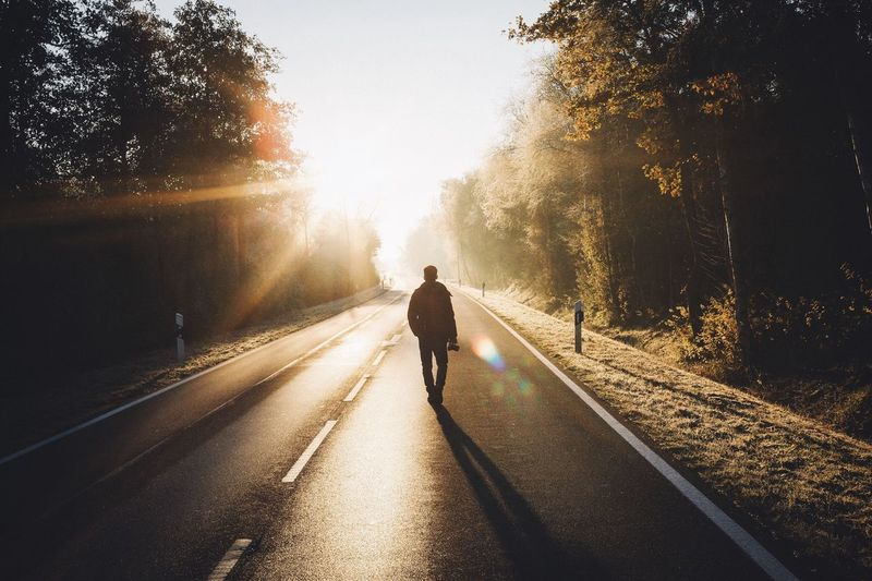 Rear view of man walking on road during sunrise