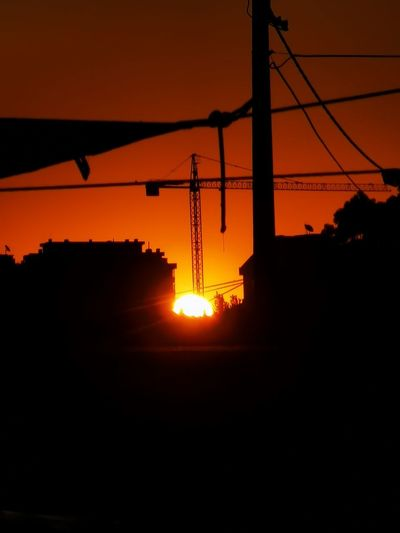 Silhouette electricity pylon against orange sky during sunset