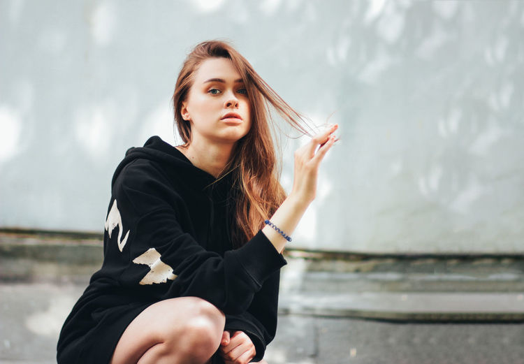 Portrait of beautiful young woman crouching outdoors
