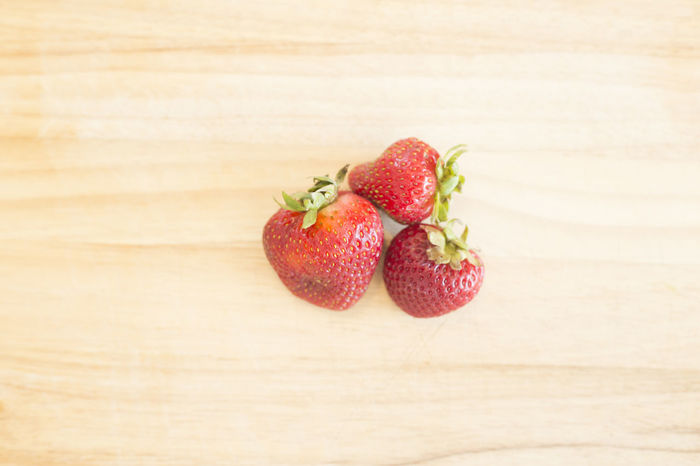 Three strawberries on a wooden background. Horizontal image. Close-up Farmstand Food Food And Drink Freshness Fruit Healthy Eating Horizontal Indoors  No People Organic Strawberries Table Three