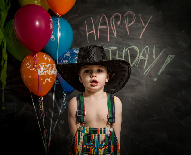 Boy Standing Against Multi Colored Balloons
