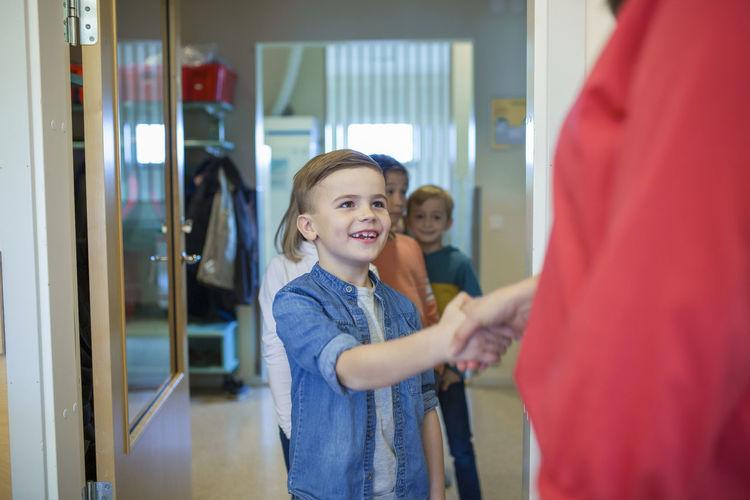 Happy friends standing in corridor