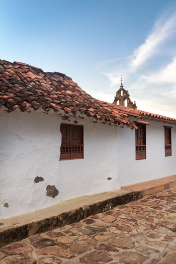 A traditional house with a church facade in the background in Guane, Colombia. Architecture Chapel Church Colombia Hiking Latin America Rural Trekking Architecture Barichara Cobblestone Colombian  Colonial Dusk Evening Guane Iglesia Santa Lucia No People Outdoors Religion Santa Lucia Church Sky South America Trek Village