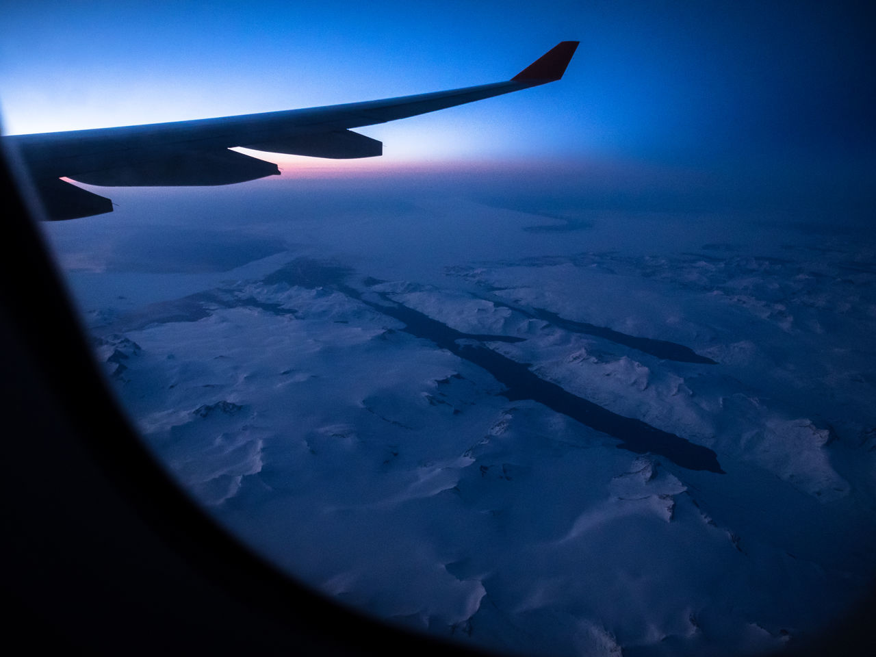 CROPPED IMAGE OF AIRPLANE WING OVER LANDSCAPE