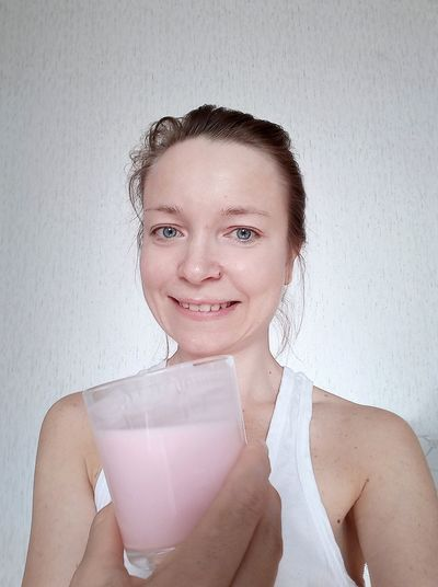 Portrait of smiling woman holding drink standing at home
