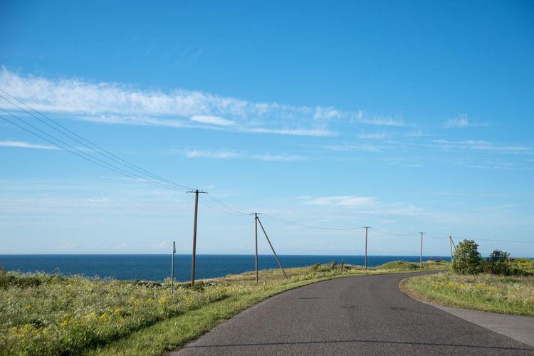 Empty coastal road against sky