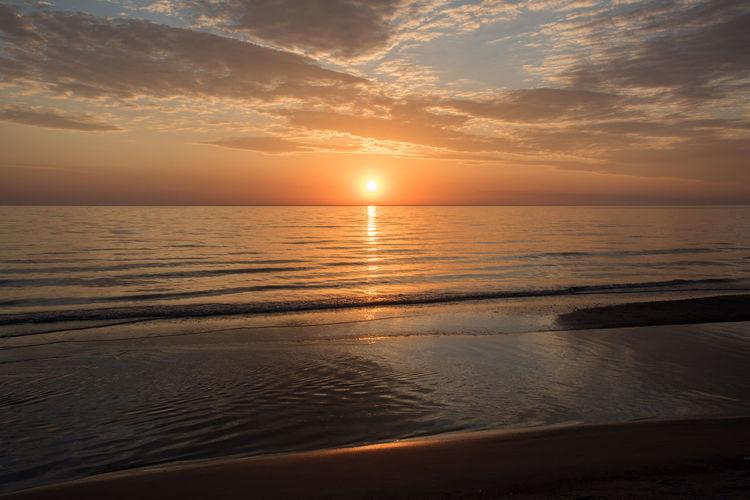 Stunning orange sunset over the peaceful Lake Michigan horizon in Bridgman, Michigan Michigan Lake Michigan Lake USA Sky Water Cloud - Sky Horizon Over Water Scenics - Nature Sunset Idyllic Sun Nature Beach Reflection Sunlight Orange Color Outdoors Tranquil Scene Beauty In Nature Tranquility Flowing Water Setting Shoreline Sand