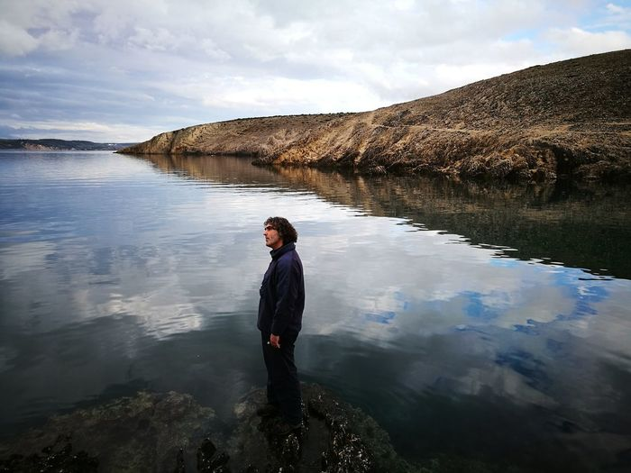 Full length of man standing in water against sky