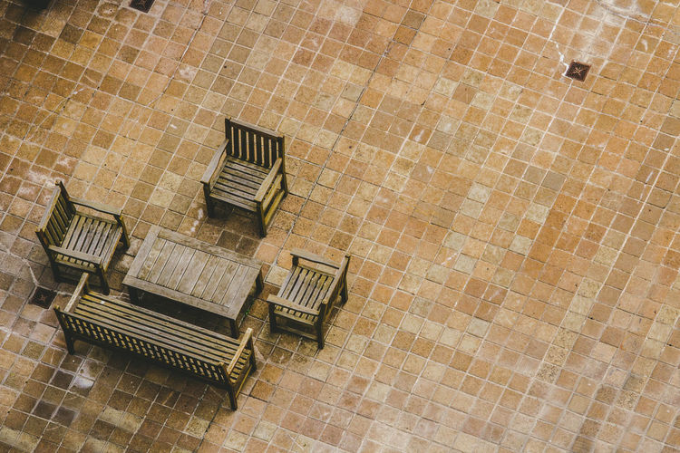 High Angle View Of Empty Chairs And Table On Footpath