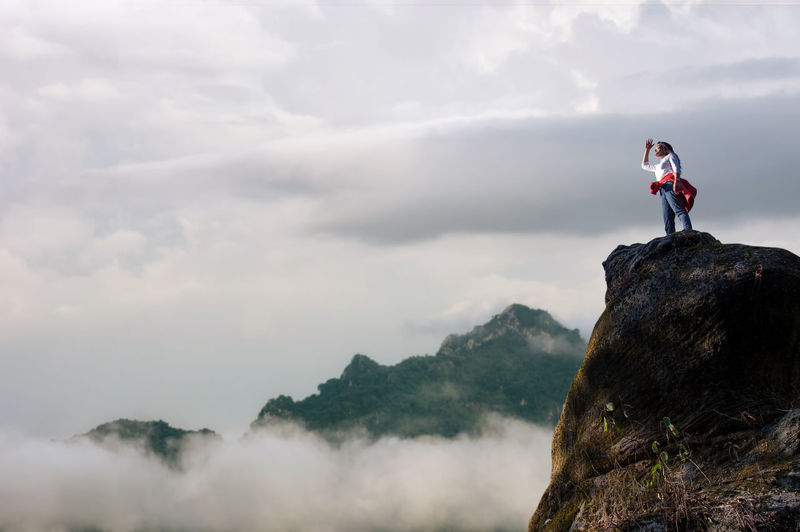 Low angle view of woman standing on cliff against sky