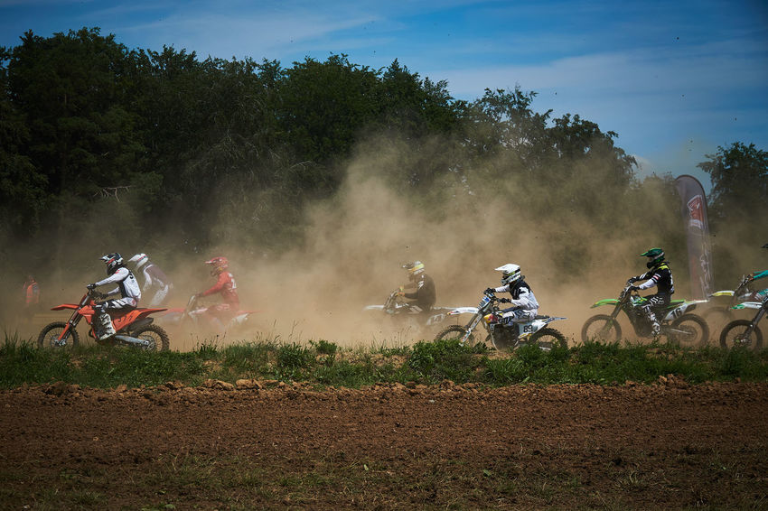 Motocross Racing Action Biker Competition Crash Helmet Day Dirt Driving Dust Extreme Sports Field Group Of People Helmet Land Land Vehicle Men Mode Of Transportation Motocross Motorcycle Nature Plant Real People Riding Sport Sports Race Transportation Tree