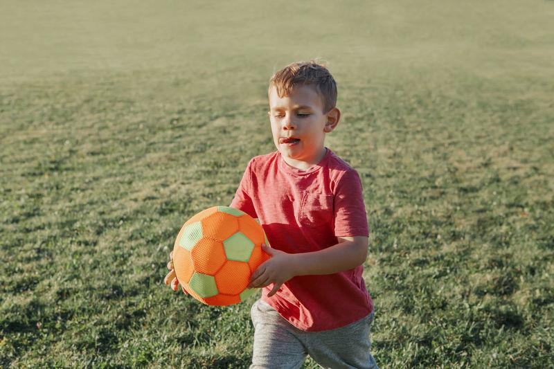 Boy holding soccer ball at park