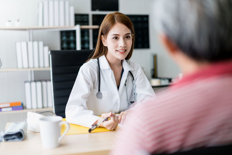 Female doctor talking with patient in hospital