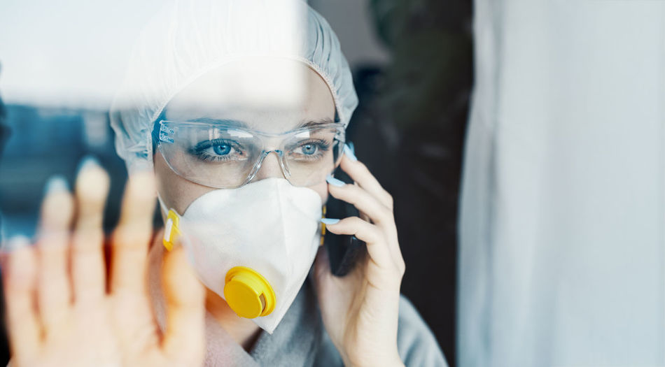 Woman talking over phone while wearing protective workwear seen through glass window