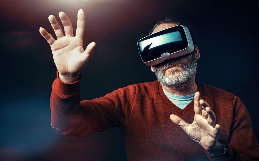 Senior man using virtual reality headset against black background