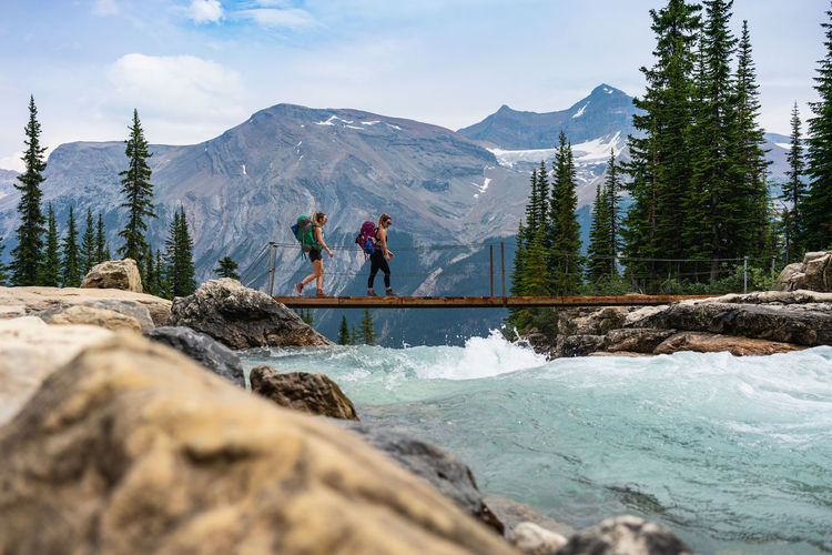 People standing on rocks by mountains against sky