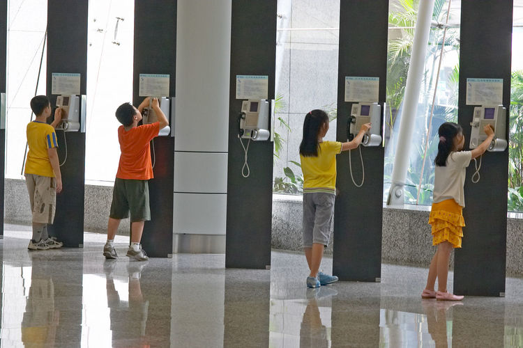 Architectural Column Casual Clothing City Life Day Kids Leisure Activity Lifestyles Medium Group Of People Modern Phone Side By Side Standing