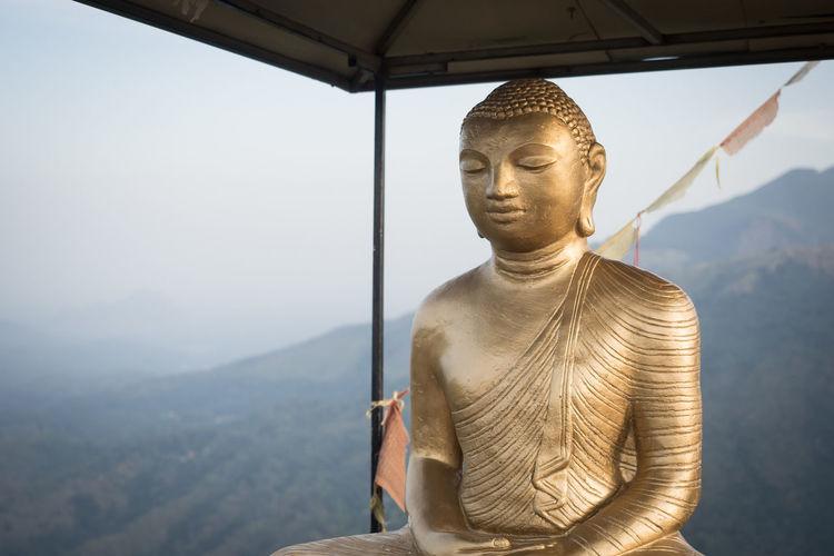 Golden buddha statue against mountain range against sky