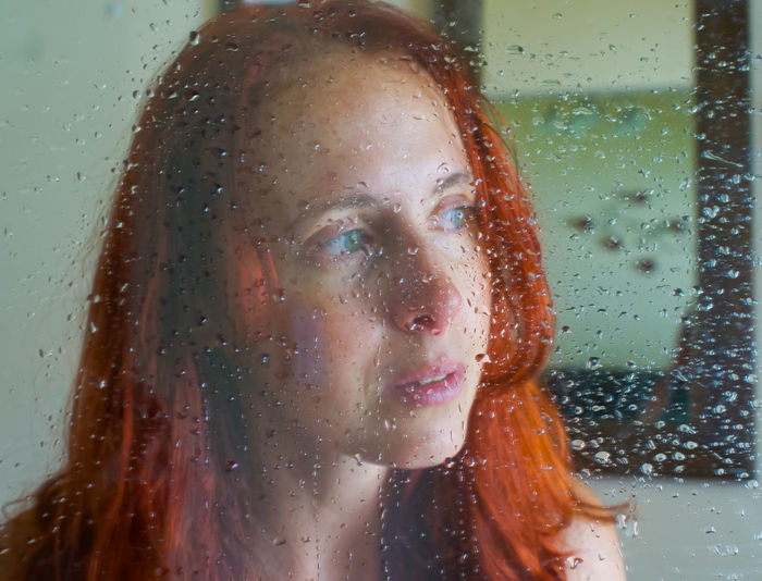 Portrait of woman with raindrops on window