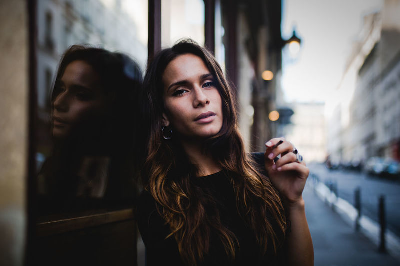 Portrait Of Young Woman Holding Cigarette While Leaning On Window