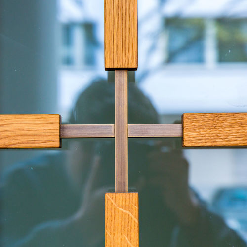Reflection Of Man Photographing Glass Window With Wooden Cross Shape