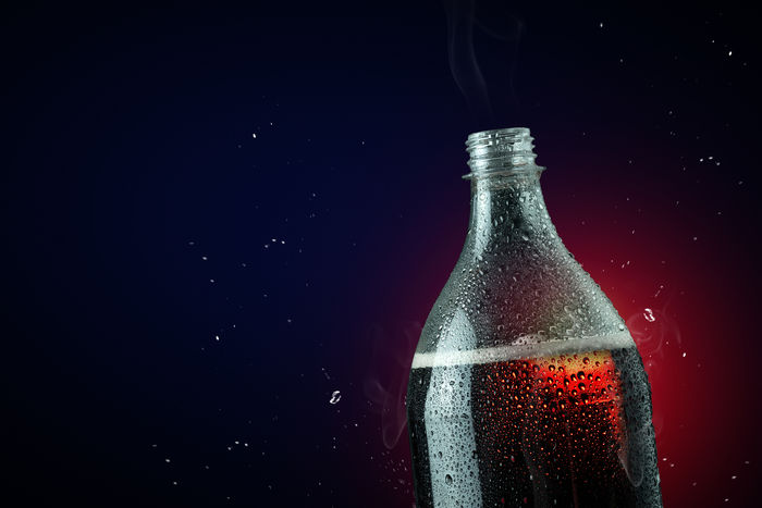 Soft drink bottle with ice splash on dark background. Studio Shot Drink Refreshment Container Bottle Alcohol Indoors  Food And Drink Close-up Glass - Material Black Background No People Water Copy Space Still Life Freshness Glass Condensation Single Object Impact Splashing Splash Cola Softdrink Softdrinks