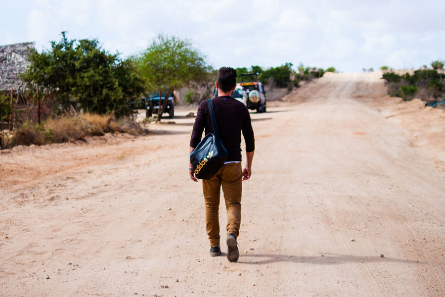 Africa Backpack Casual Clothing Country Road Day Diminishing Perspective Dirt Road Full Length Leisure Activity Lifestyles National Park Nature Nature Outdoors Rear View Road Safari Safari Animals Sky The Way Forward Tree Tsavo Vanishing Point Water Wild Animal