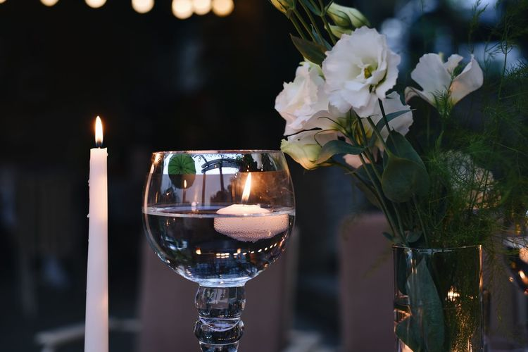 Close-up of illuminated candles on glass against blurred background