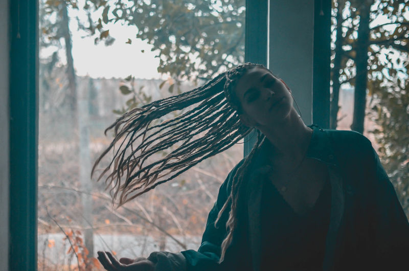 Young woman tossing hair against window