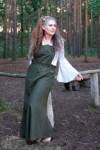 Happy woman standing by tree in forest