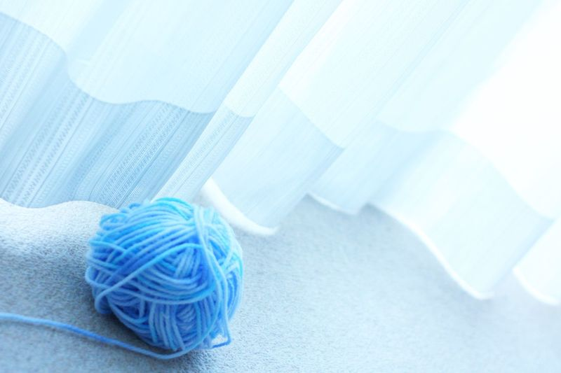 Blue Ball Of Wool By Curtain