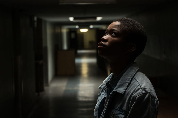Portrait of young man looking away while standing in building