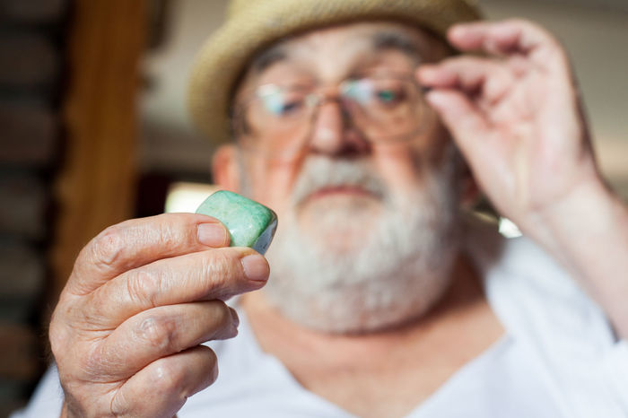 old man inspecting a precious stone Beard Close-up Eyesight Fingers Gemstone  Green Headshot Holding Human Hand Jewel Jewelry Lifestyles Looking Luxury Mineral Natural People Precious Stone Semi Precious Stones Senior Adult Senior Men Shape Size Value Weight