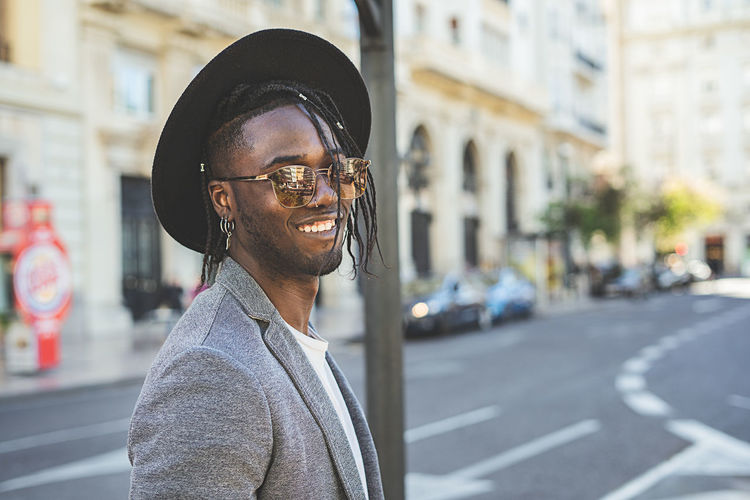 Portrait of smiling young man wearing hat while standing on street
