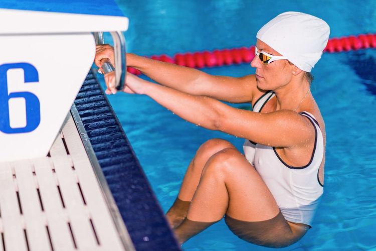 Female Swimmer Holding Diving Platform At Poolside