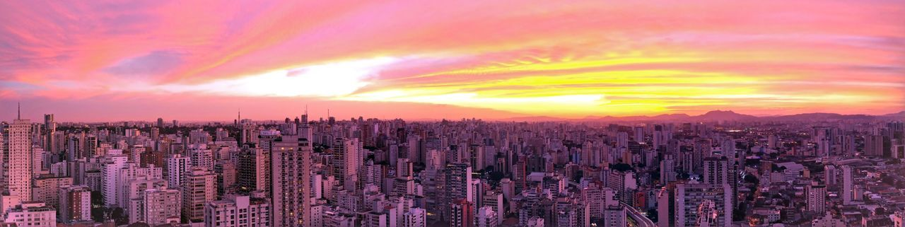 Panoramic view of city against dramatic sky during sunset
