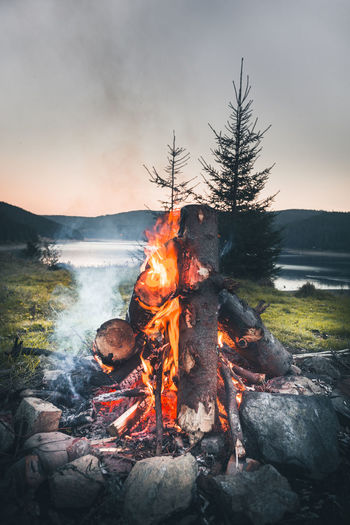 Burning Heat - Temperature Fire Flame Fire - Natural Phenomenon Nature Bonfire Log Wood Campfire Land Sky Firewood Orange Color Wood - Material Tree Glowing Environment Camping No People Outdoors Campfire Sunset Sunset_collection Lake Autumn Mood A New Perspective On Life My Best Photo