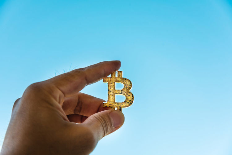 Close-up of person holding bitcoin symbol against sky