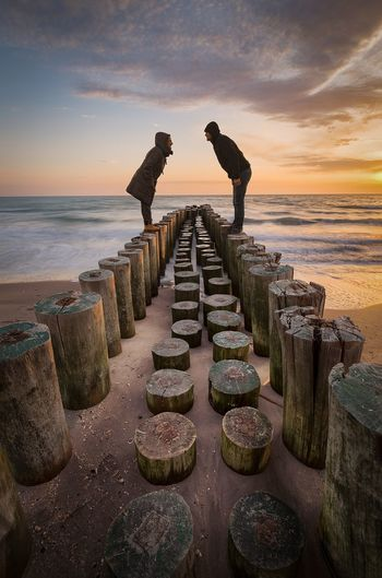 Side view full length of couple standing on wooden posts at beach during sunset