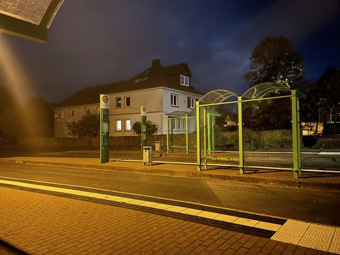 Illuminated railroad station by buildings against sky at night