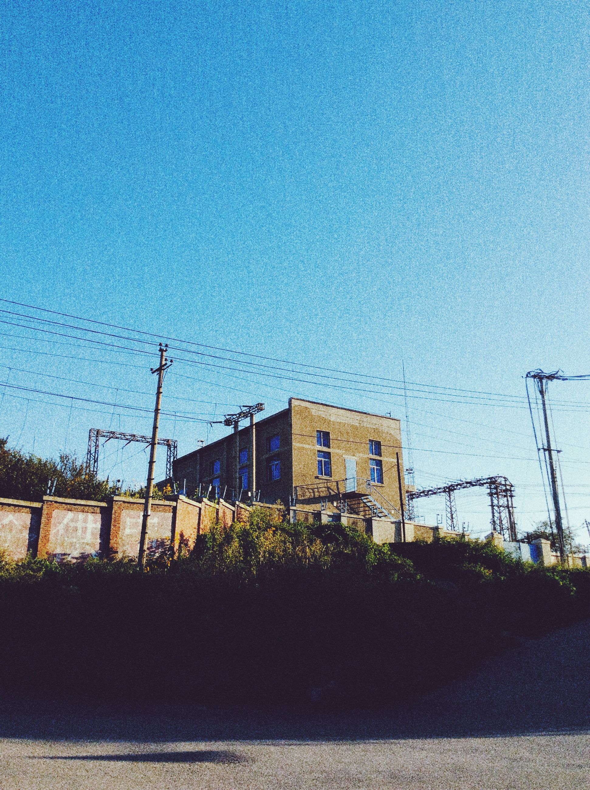 building exterior, built structure, architecture, blue, power line, clear sky, electricity pylon, house, copy space, sky, fuel and power generation, electricity, power supply, cable, low angle view, day, outdoors, no people, residential structure, field