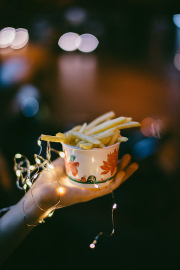 Cropped Image Of Hand Holding French Fries In Bowl With Lighting Equipment During Night Outdoors