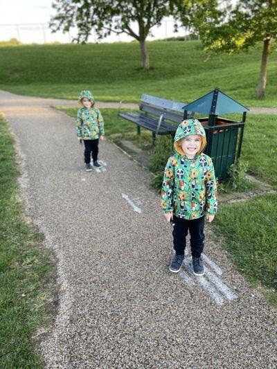 Full length of siblings walking on road