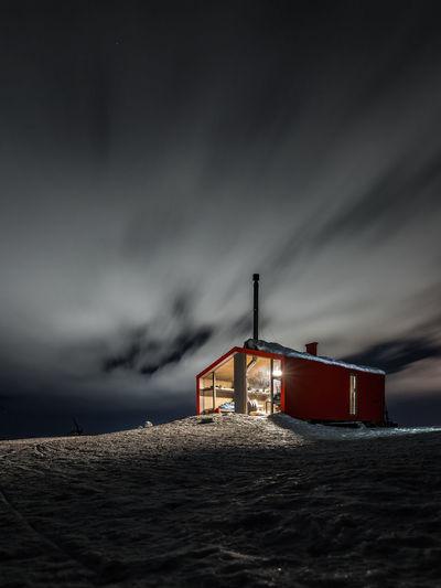 Lifeguard hut on beach against sky at dusk