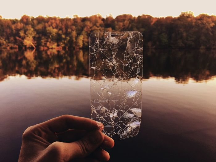 Cropped hand holding cracked glass against lake