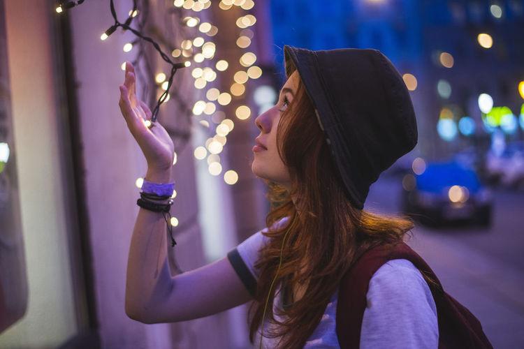Portrait of woman standing by illuminated lighting equipment at night
